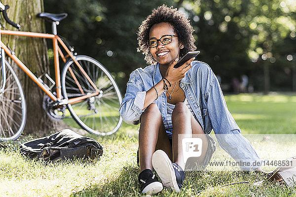 Lächelnde junge Frau ruht sich mit Handy und Tablet im Park aus
