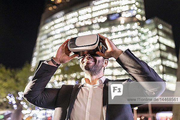 UK  London  businessman in the city wearing vr glasses by night