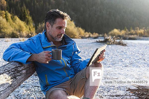 Erwachsener Mann zeltet am Flussufer und benutzt Tabletten