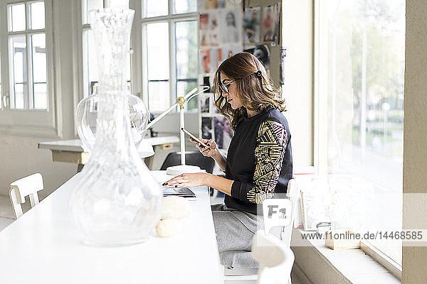 Junge Designerin benutzt Smartphone in ihrem Atelier