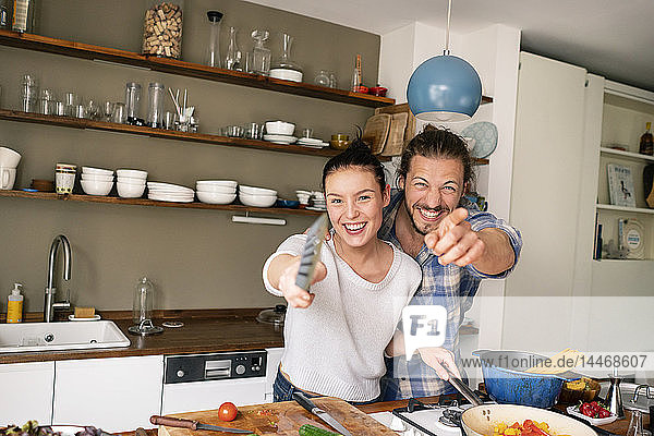 Young couple preparing food together  laughing and pointing with spatula