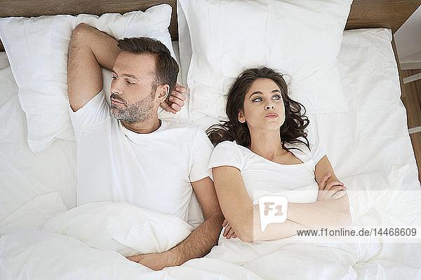 Frustriertes Paar im Bett liegend