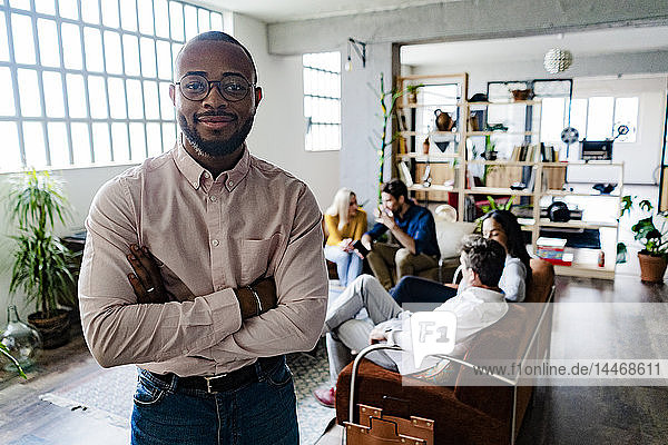 Portrait of smiling young businessman with coworkers in background in loft office