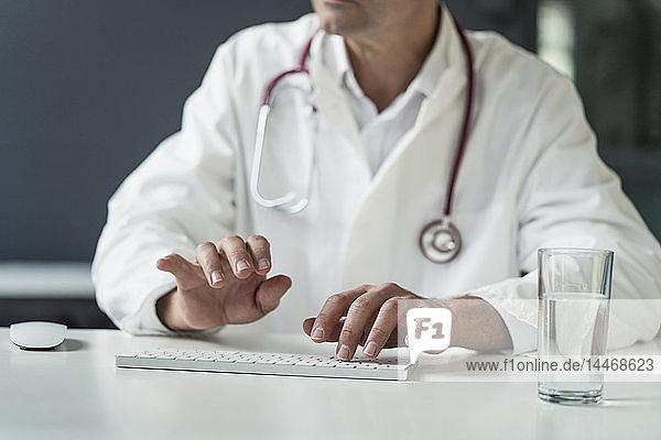 Nahaufnahme eines Arztes in medizinischer Praxis beim Tippen auf der Tastatur am Schreibtisch