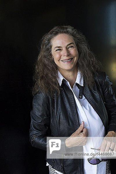 Porträt einer lächelnden reifen Frau in schwarzer Lederjacke