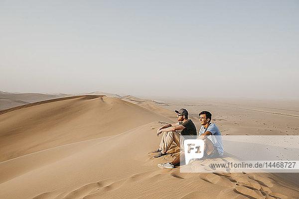 Namibia  Namib  zwei Freunde sitzen auf einer Wüstendüne und schauen sich die Aussicht an