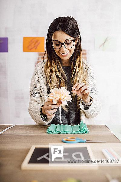 Junge Frau bastelt zu Hause  Papierblumen