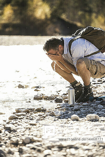 Österreich  Alpen  Mann auf Wanderung mit Rast an einem Bach