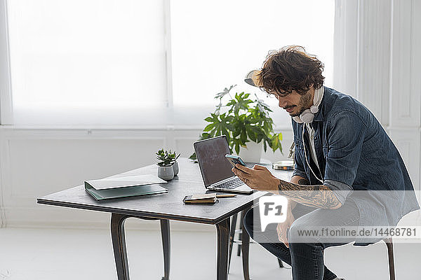 Man working in coworking space  using smartphone