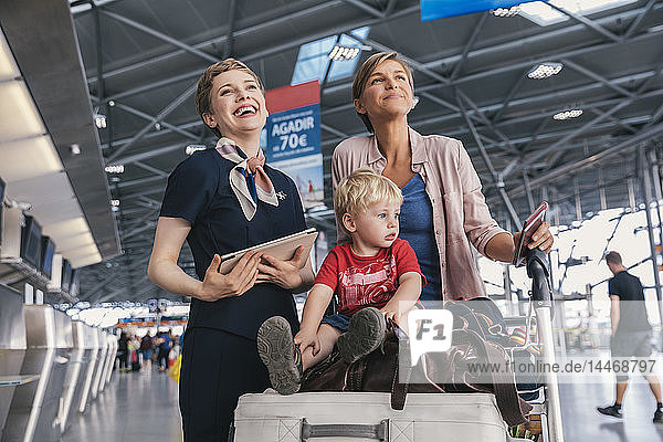 Happy airline employee with mother and child at the airport