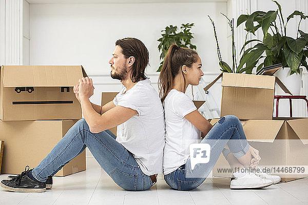 Paar mit Pappkartons auf dem Boden sitzend in neuer Wohnung