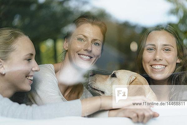 Porträt einer glücklichen Mutter mit zwei Teenager-Mädchen und Hund hinter einer Fensterscheibe