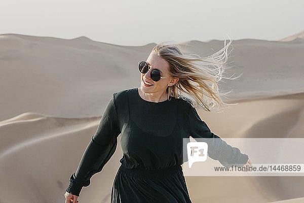 Namibia  Namib  Porträt einer lächelnden Frau mit wehendem Haar  die auf einer Wüstendüne steht
