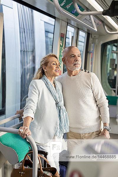 Älteres Ehepaar steht in einer Straßenbahn und sieht sich um