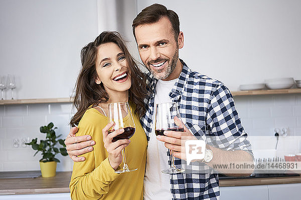 Glückliches Paar steht mit den Armen in der Küche und trinkt Rotwein