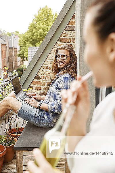Junges Paar sitzt im Sommer auf seinem Balkon  Mann benutzt Laptop