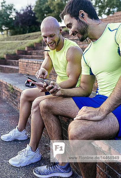 Zwei lächelnde Sportler teilen sich nach dem Training Smartphones