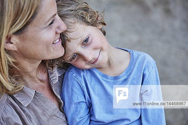 Lächelnder Junge kuschelt mit Mutter im Freien