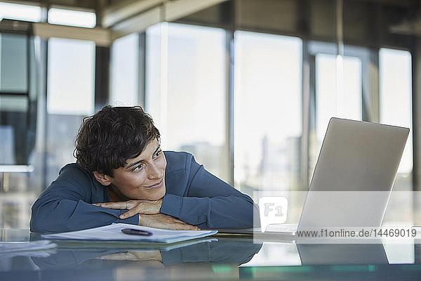 Lächelnde Geschäftsfrau lehnt im Büro auf dem Schreibtisch und schaut auf den Laptop