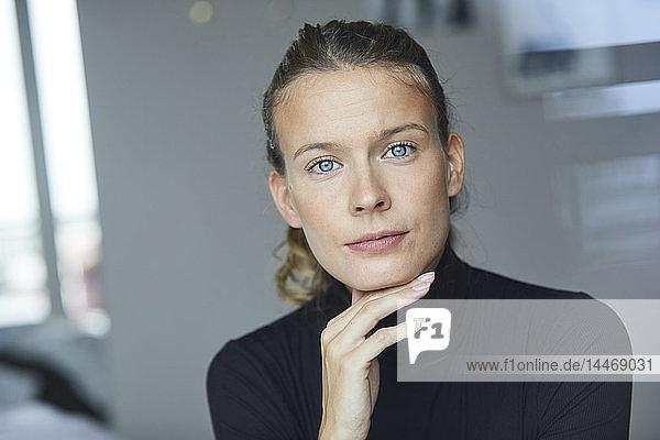 Porträt einer lächelnden jungen Frau mit schwarzem Rollkragenpullover