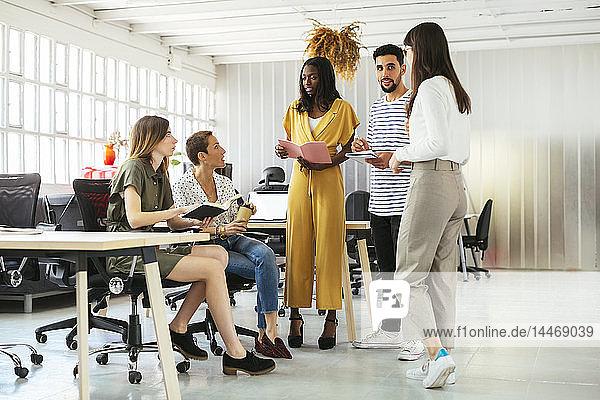 Kollegen mit Zeitplänen und Notizbüchern beim Brainstorming im Büro
