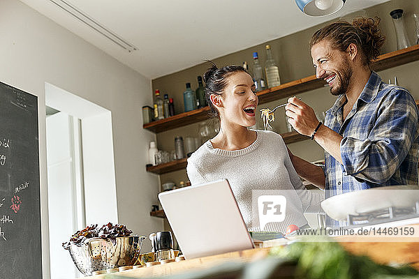 Young couple preparing spaghetti together  using online recipe