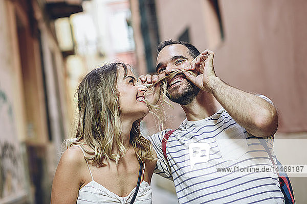 Spain  Andalusia  Malaga  funny man putting his girlfriend's hair as his mustache