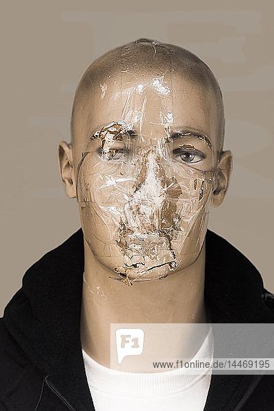 Beschädigter Kopf einer männlichen Schaufensterpuppe mit Tesafilm verklebt