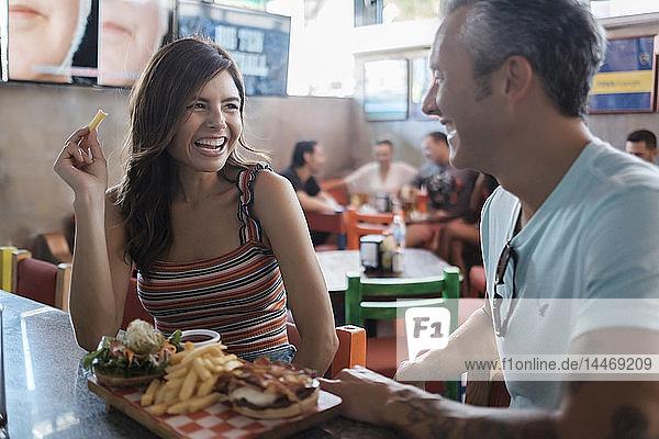 Glückliches Paar beim Hamburger und Pommes Frites in einer Bar