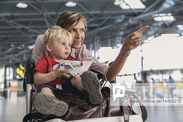 Deutschland  Köln  Porträt von Mutter und kleinem Sohn mit Gepäckwagen im Flughafenterminal