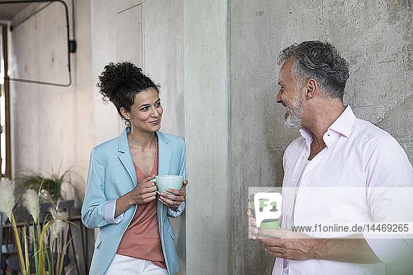 Lächelnder Geschäftsmann und Geschäftsfrau bei einer Kaffeepause in einem Loft