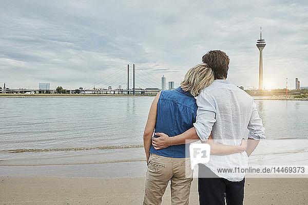 Deutschland  Düsseldorf  liebevolles junges Paar am Rheinufer