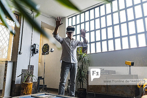 Mature man wearing VR glasses standing at the window in a loft