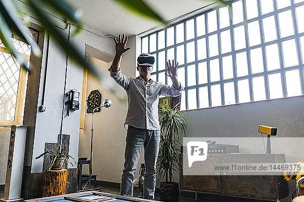 Älterer Mann mit VR-Brille steht am Fenster in einem Loft