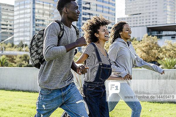 Drei Freunde rennen auf einem Rasen in der Stadt und lachen