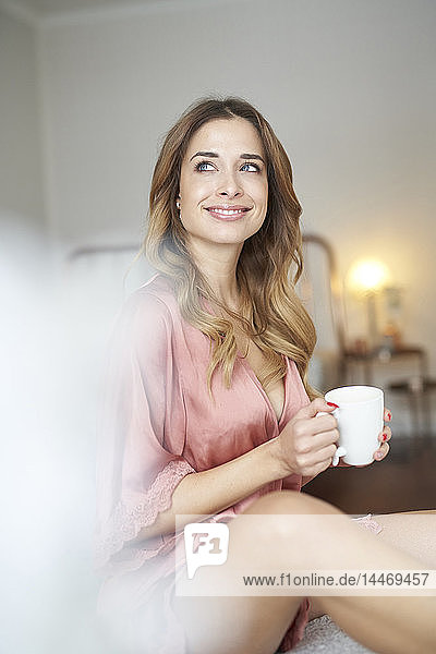 Smiling young woman in dressing gown sitting on bed with cup of coffee