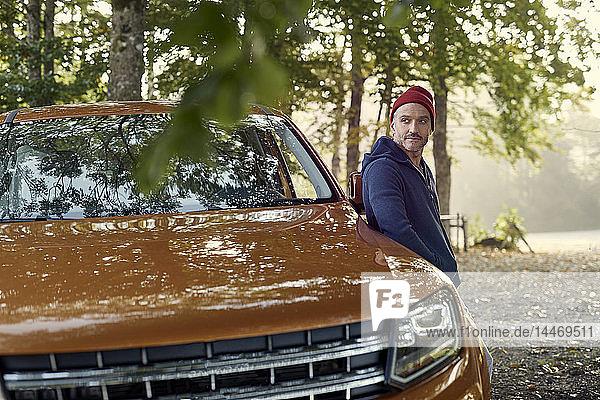 Reifer Mann lehnt sich im Wald an Auto an