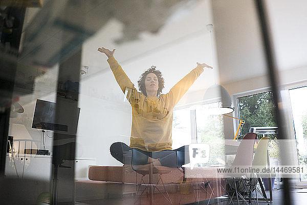 Frau sitzt zu Hause auf dem Sofa in Yoga-Pose