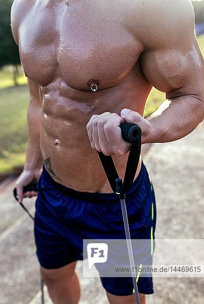 Mittelteil eines barbusigen  muskulösen Mannes  der mit Expander im Freien trainiert
