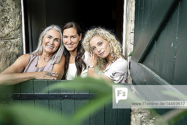 Porträt von drei lächelnden Frauen unterschiedlichen Alters hinter einem stabilen Tor