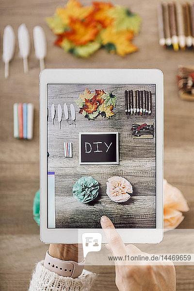 Draufsicht einer jungen Frau  die mit dem Tablett für ihren Blog Fotos von handgemachten Papierblumen macht