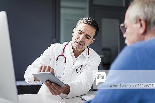 Arzt zeigt dem Patienten in medizinischer Praxis Tablette