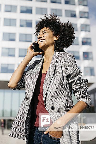Lachende Geschäftsfrau am Handy vor dem Bürogebäude