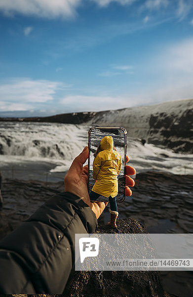 3D montage of man taking smartphone picture of Iceland's landscape and woman wearing yellow raincoat
