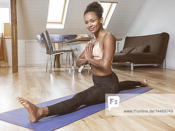 Porträt einer lächelnden jungen Frau in Yoga-Pose beim Spagat