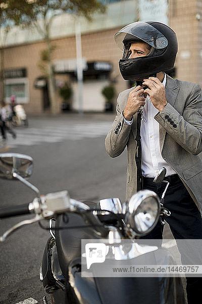Geschäftsmann neben Motorroller  der einen Helm aufsetzt