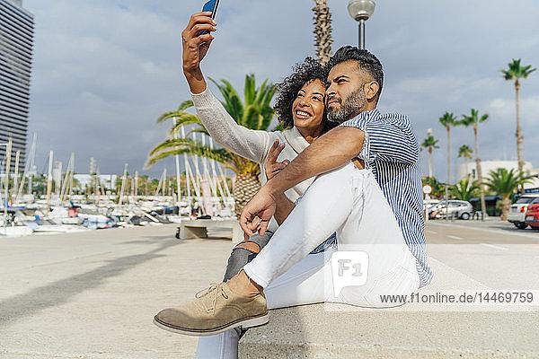 Spain  Barcelona  happy couple taking a selfie at the marina
