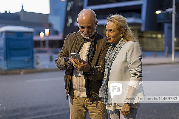 Spain  Barcelona  senior couple sharing cell phone in the city at dusk
