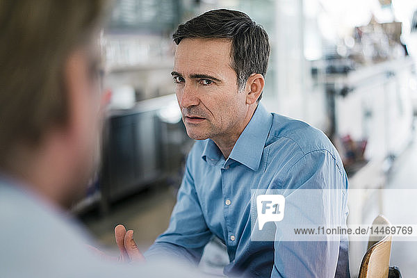 Porträt eines seriösen Geschäftsmannes,  der seinen Kollegen anschaut