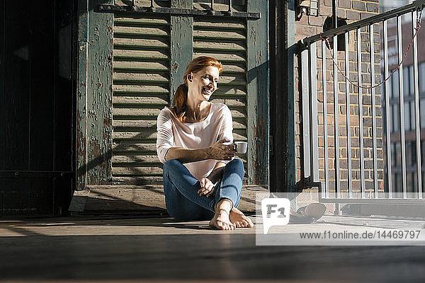 Lächelnde Geschäftsfrau sitzt barfuss mit einer Tasse Kaffee auf dem Boden